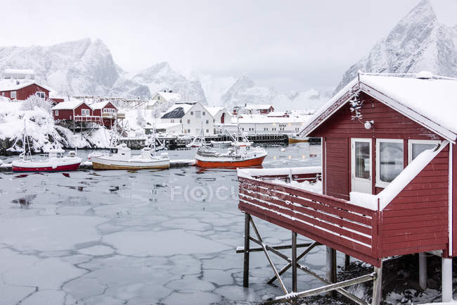 Mar helado y picos nevados alrededor de las casas típicas llamadas rorbu y barcos de pesca Hamn paisaje Islas Lofoten, norte de Noruega, Europa - foto de stock