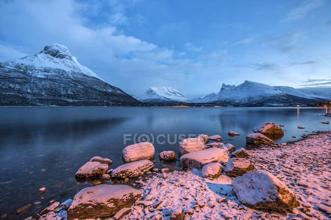 Синє небо в сутінках і снігові вершини відображені в замороженому морі Сторфьорд Лапландія Лінген Альп Troms Норвегія Європа — стокове фото