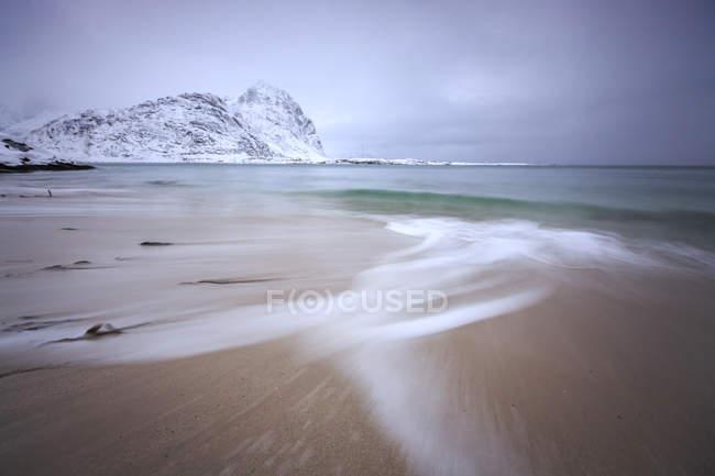 Onde del mare ghiacciato sulla spiaggia sullo sfondo le cime innevate Pollen Vareid Flakstad, Paesaggio delle Isole Lofoten, Norvegia, Europa — Foto stock