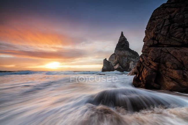 Le ciel ardent au coucher du soleil se reflète sur les vagues et les falaises de l'océan, Praia da Ursa paysage, Cabo da Roca Colares, Sintra, Portugal, Europe — Photo de stock