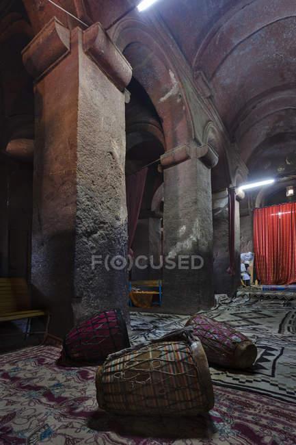 Las iglesias rupestres de Lalibela en Etiopía. Peregrino rezando frente a una iglesia. Las iglesias de Lalibela han sido construidas en los siglos XII o XIII. Han sido tallados de la roca sólida y son considerados como uno de los mon más grandes - foto de stock