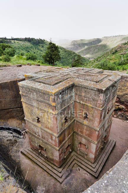 As igrejas rochosas de Lalibela na Etiópia. Peregrino rezando em frente a uma igreja. As igrejas de Lalibela foram construídas no século XII ou XIII. Eles foram cortados da rocha sólida e são considerados um dos maiores mon — Fotografia de Stock
