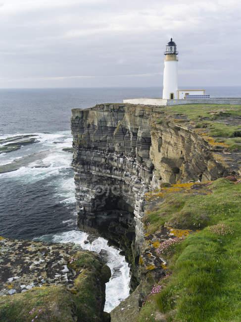 Los acantilados en Noup Head con faro de cabeza nupcial en la isla de Westray en las Islas Orcadas. Los acantilados se extienden por millas, son el hogar de una de las colonias de aves marinas más grandes del Reino Unido y son una reserva RSPB. europa, europa central, norte de eu - foto de stock