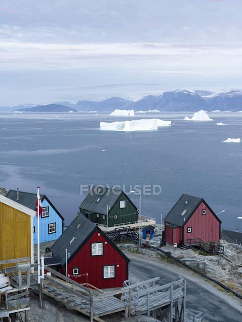 Piccola città Uummannaq nel nord della Groenlandia occidentale. Sullo sfondo la penisola glaciata di Nuussuaq (Nugssuaq). America, Nord America, Groenlandia, Danimarca — Foto stock