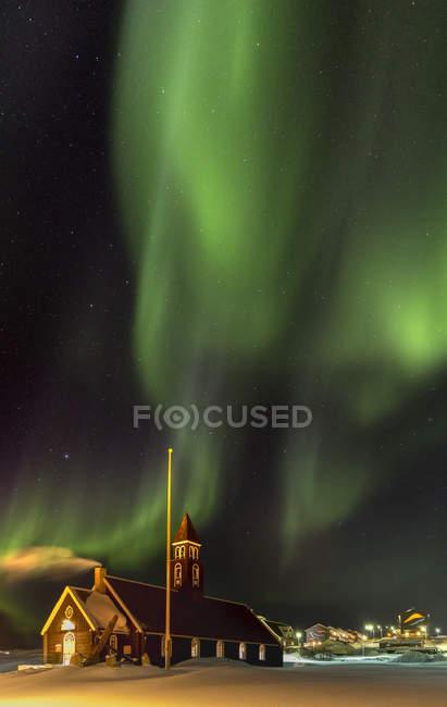 Северное сияние над Сионской церковью. Town Ilulissat at at the shore of Disko Bay in West Greenland, center for tourism, administration and economy. Близлежащий ледник включен в список Всемирного наследия ЮНЕСКО. Америка, Северная Америка, Гренландия, Дания — стоковое фото