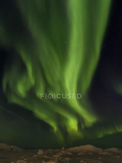Luces boreales sobre la orilla de la bahía congelada de Disko. Town Ilulissat at the shore of Disko Bay in West Greenland. El fiordo de hielo cercano está catalogado como patrimonio mundial de la UNESCO. América, América del Norte, Groenlandia, Dinamarca - foto de stock