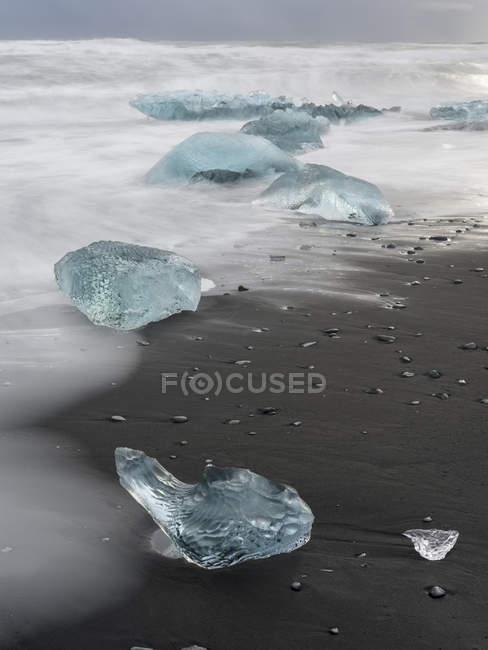 Iceberg sulla spiaggia vulcanica nera. Spiaggia dell'Atlantico settentrionale vicino alla laguna glaciale Joekulsarlon e al ghiacciaio Breithamerkurjoekull nel Vatnajoekull NP.europe, Europa settentrionale, Islanda, febbraio — Foto stock