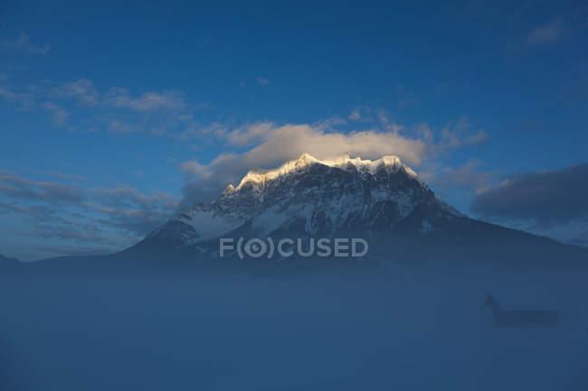 Chaîne de montagne de Wetterstein avec Mt. Zugspitze d'Ehrwald, Autriche. La nuit tombe sur la chaîne de montagne. Zugspitze, la plus haute montagne d'Allemagne, est en arrière-plan à gauche. Le téléphérique d'Ehrwald à Zugspitze est visible sur la gauche. le — Photo de stock
