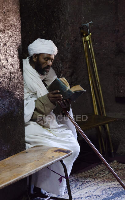 The rock-hewn churches of Lalibela in Ethiopia. Pilgrim praying in front of a church.  The churches of Lalibela have been constructed in the 12th or 13th century. They have been hewn from the solid rock and are considered to be one of the largest mon — Stock Photo
