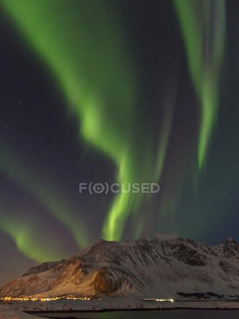 Северное сияние над Флакстадоей и деревней Рамберг. Лофотенские острова в северной Норвегии зимой. Европа, Скандинавия, Норвегия, февраль — стоковое фото