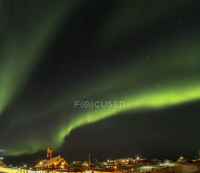 Northern Lights sobre a cidade e congelado Disko Bay. Cidade Ilulissat na costa da Baía de Disko, na Groenlândia Ocidental, centro de turismo, administração e economia. O fiorde de gelo nas proximidades está listado como patrimônio mundial da UNESCO. América do Norte, Gronelândia — Fotografia de Stock