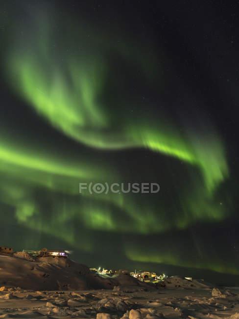 Northern Lights sobre la ciudad y la bahía de Disko congelada. Town Ilulissat en la orilla de la bahía de Disko en el oeste de Groenlandia, centro de turismo, administración y economía. El fiordo de hielo cercano está catalogado como patrimonio mundial de la UNESCO. América, Norteamérica, Groenlandia, Den - foto de stock
