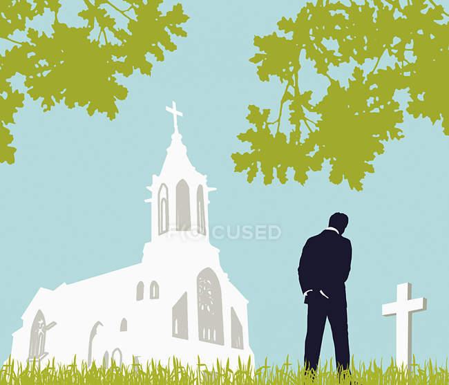 Hombre visitando cementerio cerca de la iglesia - foto de stock