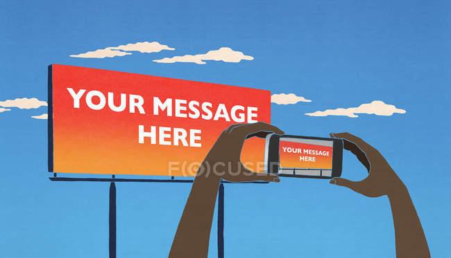 Принимая сотовый телефон фотография рекламного щита говорят ваше сообщение здесь — стоковое фото