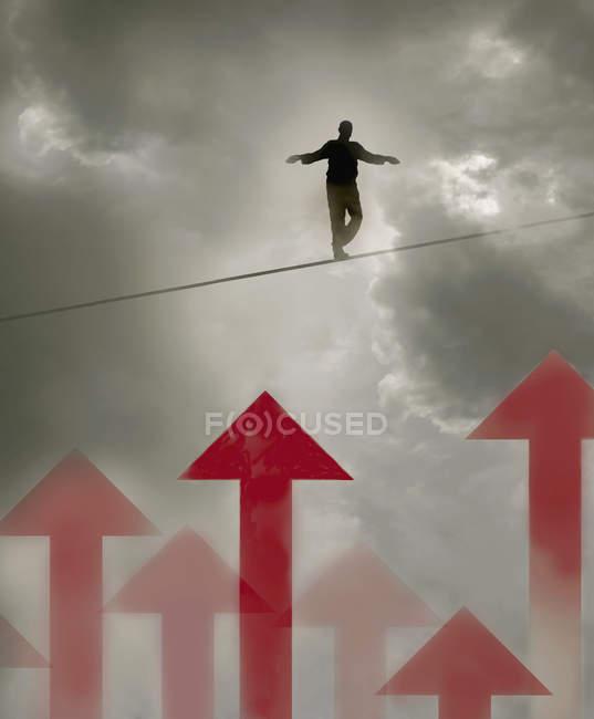 Homem caminhando corda bamba sobre setas no céu nublado — Fotografia de Stock