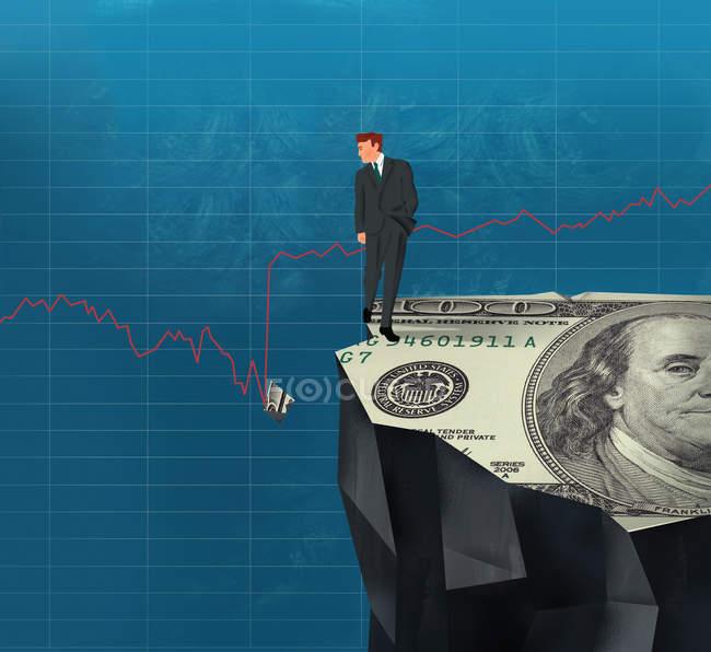 Empresario en el acantilado mirando pedazo roto de billete de dólar en el gráfico de línea - foto de stock