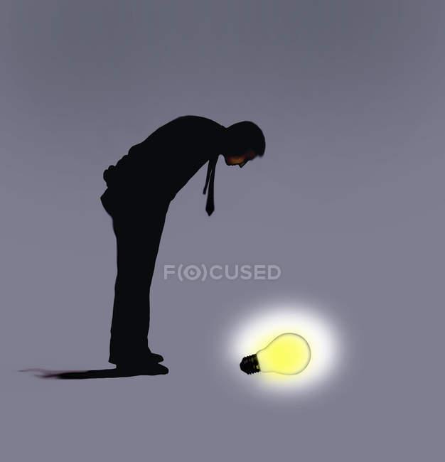Homme regardant vers le bas sur l'ampoule rougeoyante — Photo de stock