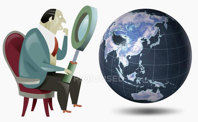 Empresario mirando al globo con lupa - foto de stock
