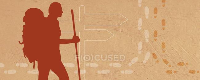Силуэт туриста на указателе, окруженном следами — стоковое фото