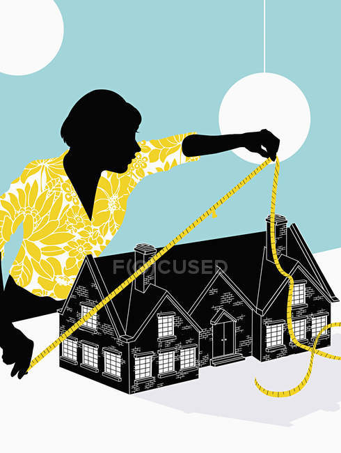 Woman measuring house on blue background — Stock Photo