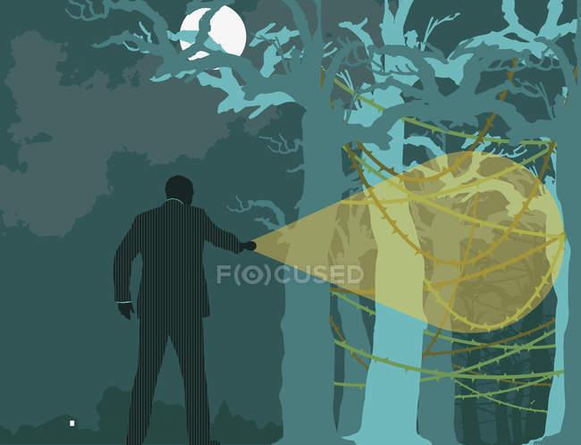 Geschäftsmann sucht nachts Wald ab — Stockfoto