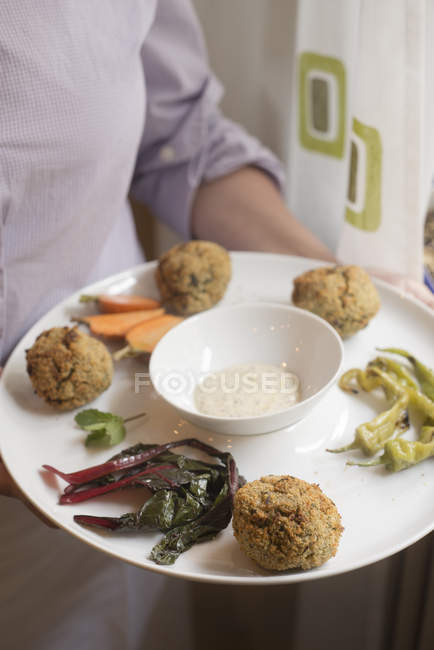 Potato and spelt no-meatballs with vegetables served with yogurt and mustard sauce. — Stock Photo