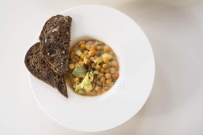 Kichererbsen und Gemüsesuppe mit Brotscheiben serviert, Ansicht von oben. — Stockfoto