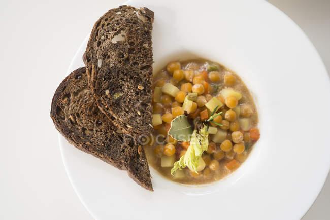 Нут і овочевий суп подається з скибочками хліба, вид зверху. — стокове фото