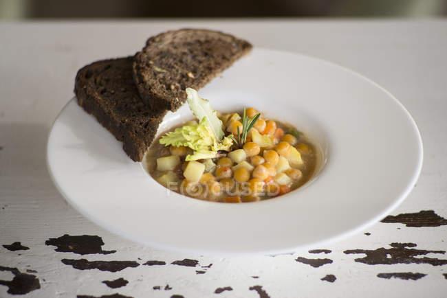 Kichererbsen und Gemüsesuppe mit Brotscheiben. — Stockfoto