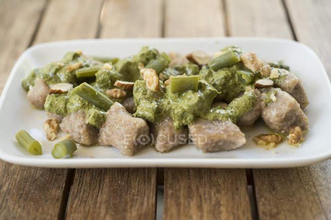 Лобода і картопляних галушки з веганом песто на тарілці. — стокове фото