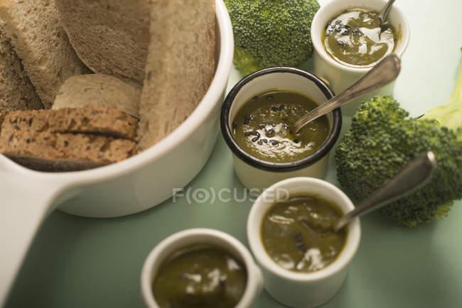 Чашки свіжого пюре з брокколі з мискою нарізаного хліба. — стокове фото