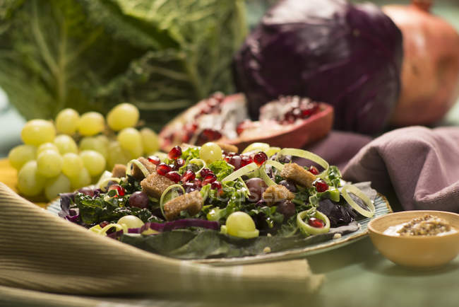 Autumnal salad with grapes, pomegranate seeds and vegetables. — Stock Photo