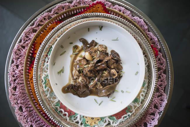 Соєвий тушковане з грибами і зеленню на вінтажній тарілці, вид зверху. — стокове фото