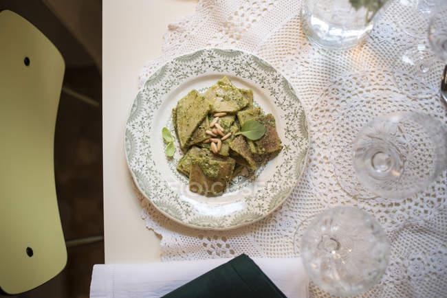 Паста грубого помелу з вершковим соусом рукола з базиліком і кедровими горіхами на вінтажній тарілці — стокове фото