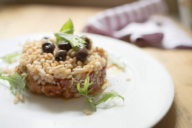 Gerstenkuchen mit würzigem Sojaeintopf und marinierten Oliven auf dem Teller. — Stockfoto