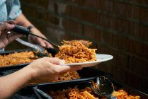 Persona che serve Maccheroni e salsa di pomodoro pasta preparata su piatto, catering cibo — Foto stock