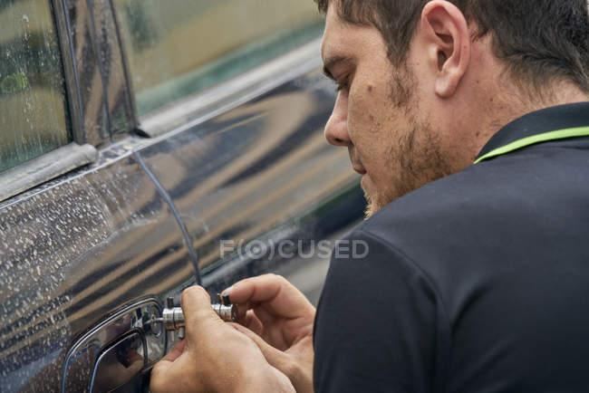 Hombre usando llave especial para arreglar azul sucio puerta del coche - foto de stock