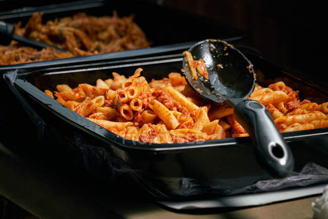 Macaroni and tomato sauce prepared pasta, catering food and plastic spoon — Stock Photo