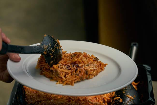 Person, die Macaroni und Tomatensauce zubereitet Pasta auf Teller, Catering-Lebensmittel — Stockfoto