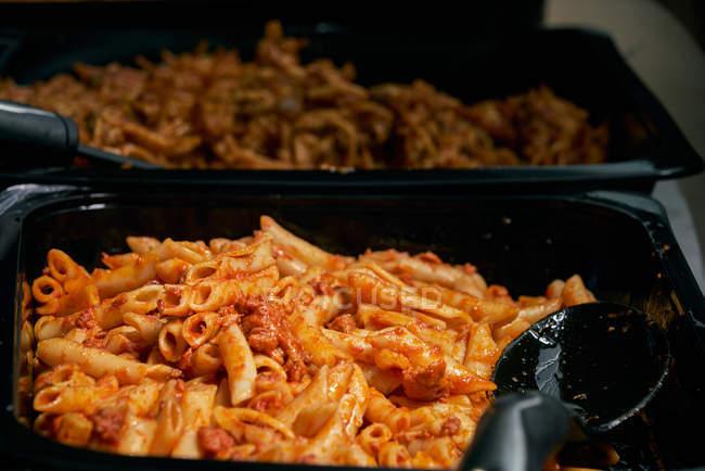 Macaroni und Tomatensauce zubereitet Pasta, Catering-Lebensmittel und Kunststofflöffel — Stockfoto