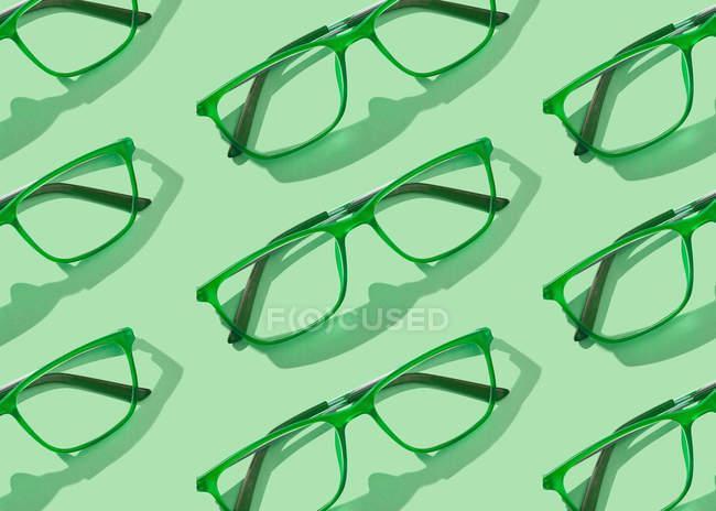 Konzeptionelles Bild von Brillensammlungen auf grünem Hintergrund — Stockfoto