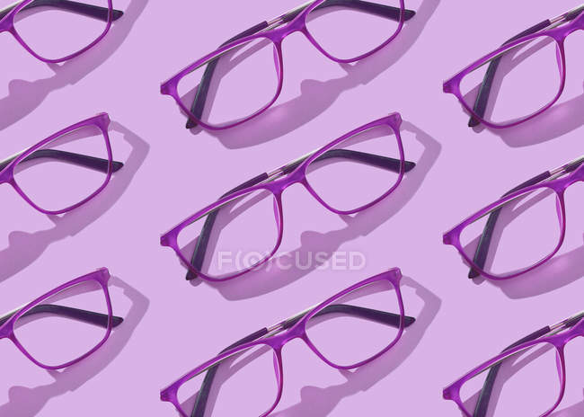 Conceptual image of glasses collections on purple background — Stock Photo