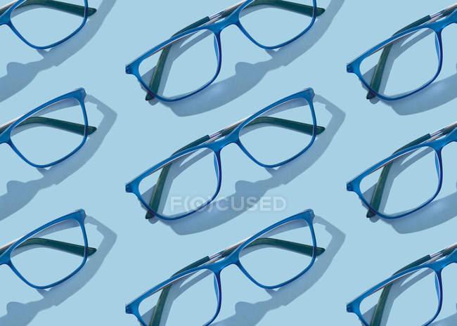 Konzeptionelles Bild von Brillensammlungen auf blauem Hintergrund — Stockfoto