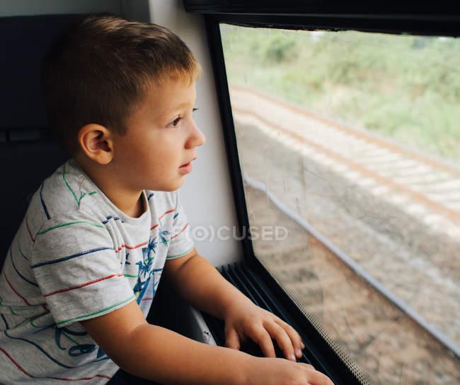 Junge schaut durch das Zugfenster aufgeregt über Reise — Stockfoto