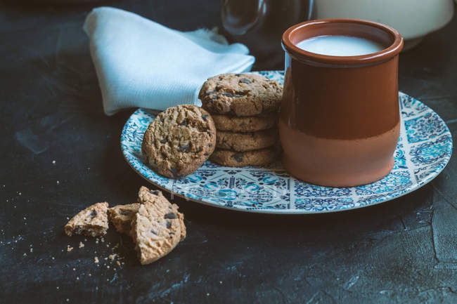 Clay jar with milk and baked cookies - foto de stock