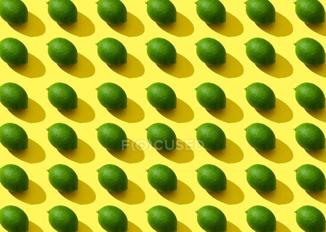 Citrons verts sur la surface jaune, fond horizontal — Photo de stock