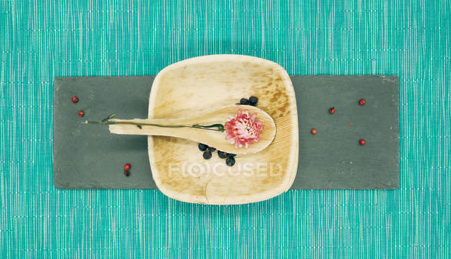 Still life of dry flower on spoon on wooden plate — Stock Photo