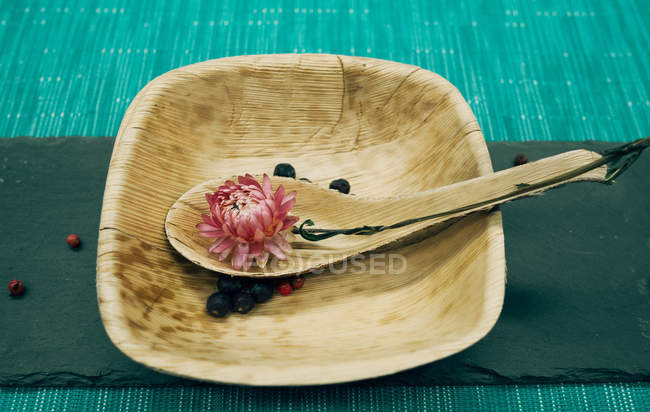 Still life of dry pink flower on spoon on wooden plate — Stock Photo