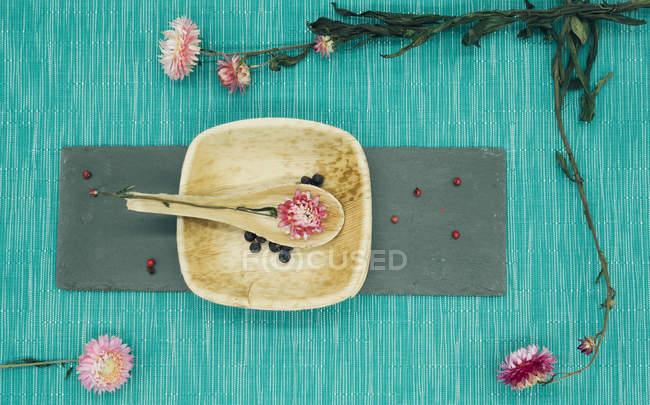 Still life of dry pink flowers on spoon on wooden plate — Stock Photo