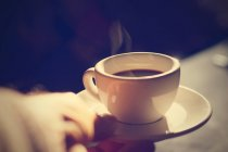 Male hand holding cup of coffee — Stock Photo